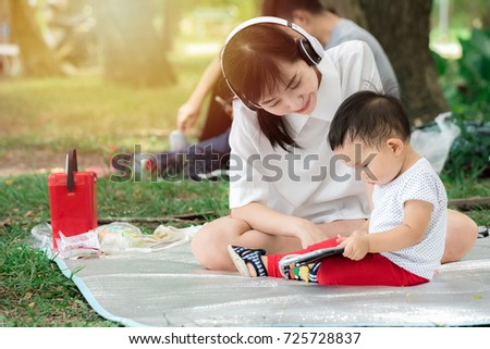 beautiful young mother with her son listening to music in the park, mother and baby playing outdoor at park