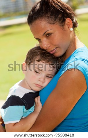Beautiful young multicultural woman and boy in a outdoor park setting.