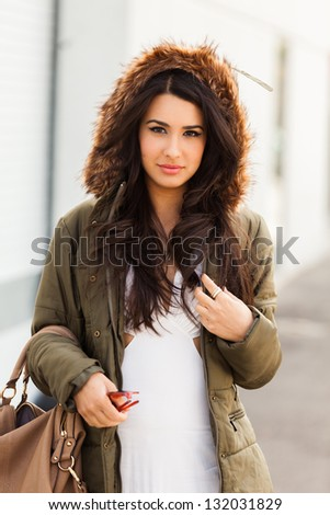 Beautiful young multicultural woman outdoors wearing a winter fur coat.