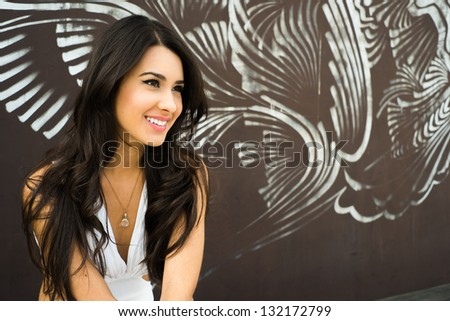 Beautiful young multicultural woman outdoors with a graffiti background. - stock photo
