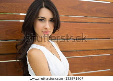 Beautiful young multicultural woman outdoors with a wooden background.