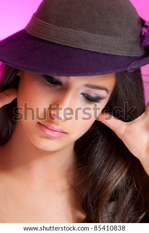 Beautiful young multicultural woman wearing a hat in a studio pose with purple background.