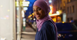 Beautiful young Muslim woman in urban setting smiling at camera