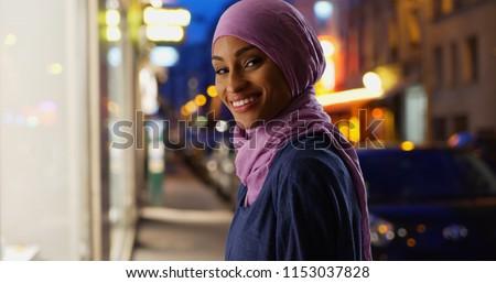 Beautiful young Muslim woman in urban setting smiling at camera