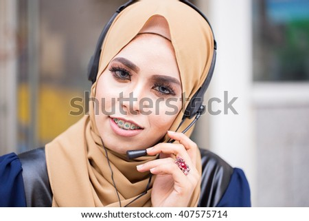 Beautiful young muslim  woman operator with headset