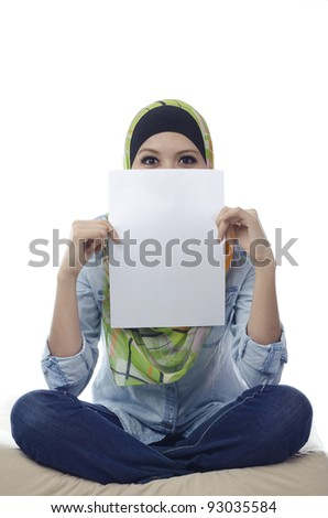Beautiful young muslim woman seat and holding a blank paper.half face covered by blank paper
