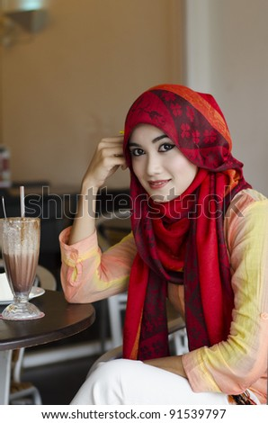 beautiful young muslim woman with stylish scarf smiling and enjoy chocolate drink in the coffee shop