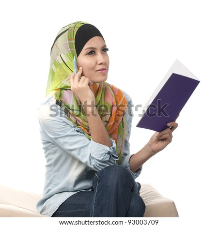 Beautiful young muslim women thinking while read a book. Isolated on white background.