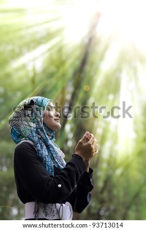 beautiful young muslimah woman with head scarf standing and praying under rays of light