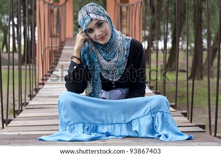 beautiful young muslimah women with stylish head scarf sit on the hanging bridge at recreation park
