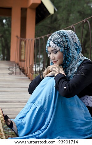 beautiful young muslimah women with stylish head scarf smiling sit on the hanging bridge at recreation park with close eyes