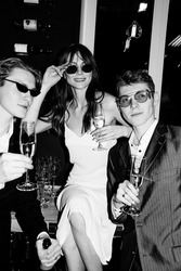 Beautiful young people, a girl and two male twins celebrating. Champagne in hands, happy emotions, New Year's mood. Retro style, black and white photo, camera flash