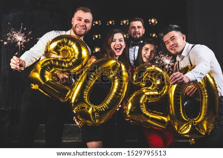 Beautiful young people at a corporate party holding balloons 2020. Happy New Year celebration. Club party with friends