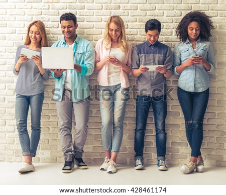 Beautiful young people of different nationalities are using gadgets and smiling, standing against white brick wall