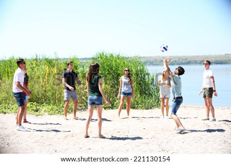 Beautiful young people playing volleyball on beach