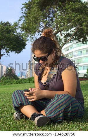 Beautiful young Peruvian woman text messaging on mobile phone in park (Selective Focus, Focus on the face and the hands of the woman)
