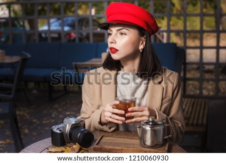 Beautiful young photographer drinking hot tea in a cafe #1210060930