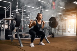 Beautiful young powerlifter squatting in modern fitness studio using heavy barbell, looking aside expressing self assurance, professional sport concept, white smoke in the air