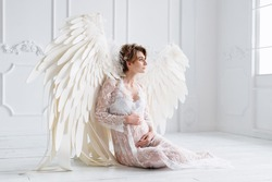 Beautiful young pregnant girl with big angel wings in white studio.