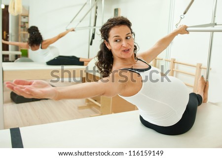 Beautiful young pregnant lady doing pilates in her last week before delivery.