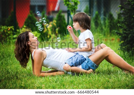 Beautiful young pregnant woman and her older child, lying down in the grass, making soap bubbles in garden