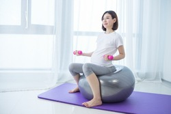 beautiful young pregnant woman doing exercise at home on fitball