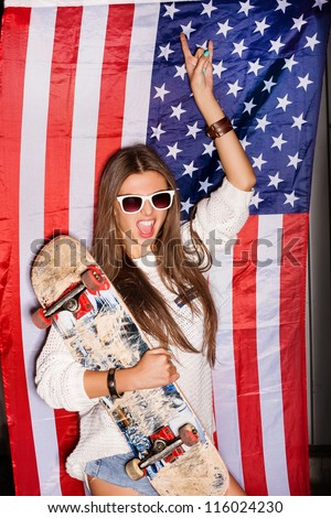 beautiful young pretty woman in sunglasses with national usa flag in background - stock photo