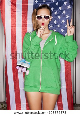 beautiful young pretty woman in sunglasses with national usa flag in background, sucking a lollipop