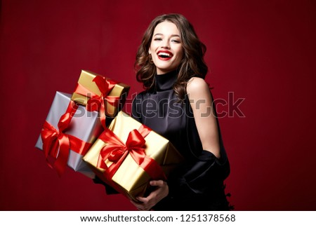 Beautiful young pretty woman with a bright evening make-up of shiny red lipstick on the lips brunette curly hair festive mood winter Christmas New Year St. Valentine's Day and birthday gift surprise.