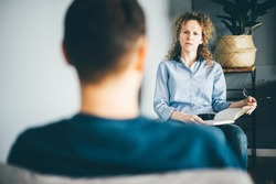 Beautiful young psychotherapist is making notes, and listening man. Psychotherapist consulting man, asking questions, interviewing man sitting on chair. Psychologist with client.