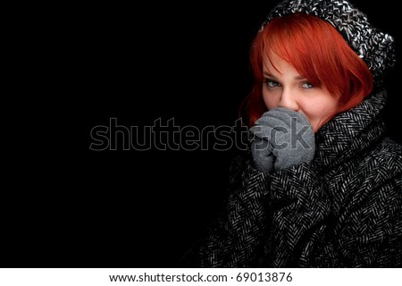 beautiful young red hair woman wearing a warm winter hat and coat, black background