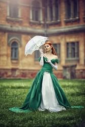 Beautiful young red-haired girl in a medieval green dress.
