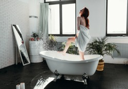 Beautiful young red-haired slim woman covering her body with towel and smiling while standing in bathtub in spacious modern bathroom with green plants and window.