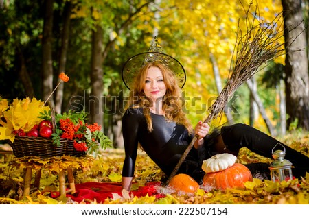Beautiful young red-haired witch with a broom sitting in the autumn forest on a holiday Halloween