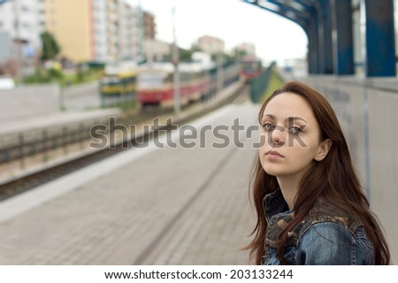 Beautiful young red haired woman with a sad facial expression waiting alone on the platform of a railway station