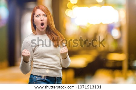 Beautiful young redhead woman happy and excited celebrating victory expressing big success, power, energy and positive emotions. Celebrates new job joyful at night #1071513131