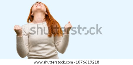 Beautiful young redhead woman happy and excited expressing winning gesture. Successful and celebrating victory, triumphant isolated over blue background