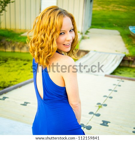 Beautiful young redhead woman in blue dress posing outdoors and looking over her shoulder - stock photo