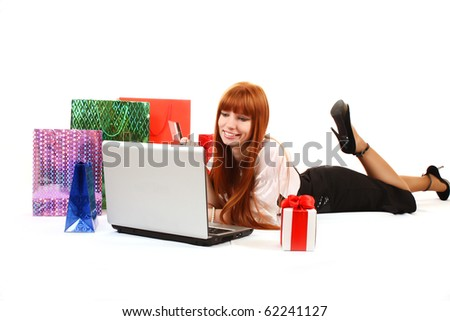 Beautiful, young, redhead woman with color shopping bags shopping over internet. On white background