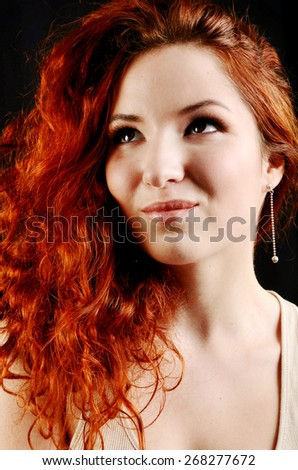 Stock Photo Beautiful young redhead woman with perfect daytime makeup and long silver earrings smiling playfully