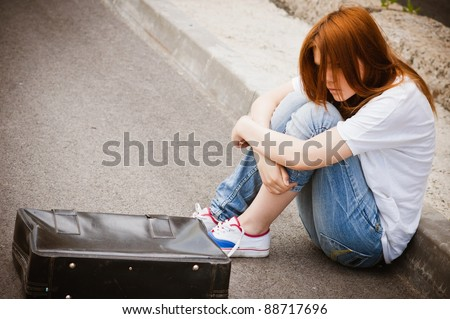 Beautiful young sad girl sitting on the asphalt