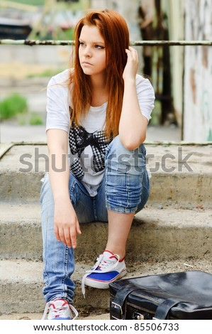 Beautiful young sad girl sitting on the staircase