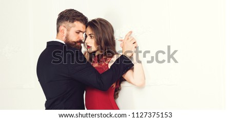 Beautiful young sensual couple holding hands leaning on wall, loving brutal bearded man and affectionate woman getting closer to kiss each other teasing enjoying tenderness and intimacy feeling desire #1127375153
