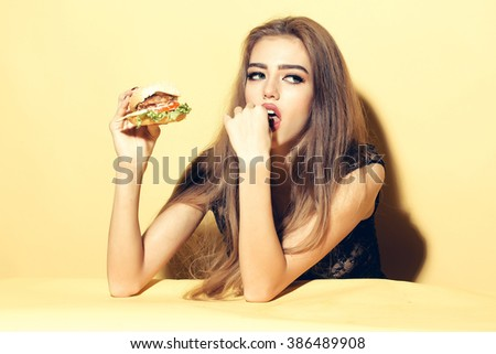Beautiful young sensual woman eating tasty big fresh burger indoor on studio yellow background, horizontal picture