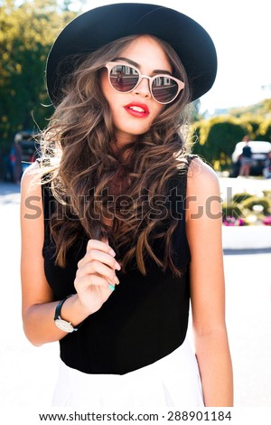 Beautiful young sexy brunette girl with long curly hair with bright evening make-up,wearing a slinky silk dress high heels a little bag necklace,wealth and luxury,party background baroque.Street style