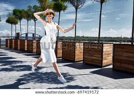 Beautiful young sexy brunette woman dressed white cotton sarafan dress straw hat sneakers style comfortable clothes for visits walks around the summer city travels adventure tourist rides around jump. #697419172