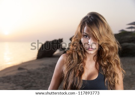 Beautiful young sexy fashion model in jeans by the sea at sunrise