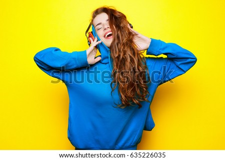 Beautiful young sexy girl DJ in a blue jacket listening music in red headphones on a yellow background and having fun - Shutterstock ID 635226035