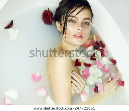 Beautiful young sexy girl with dark hair wet, evening makeup, takes bath with milk tan perfect farfor skin in romantic atmosphere, beauty cosmetic salon and spa for woman at Valentine\'s Day