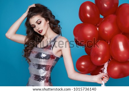Beautiful young sexy girl with long hair brunette woman with evening make-up cosmetics dressed in a blue silk dress holding in hand many red balloons party Valentine's Day heart and love #1015736140